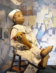 photo fo Robert the doll in his sailor outfit with small stuffed dog