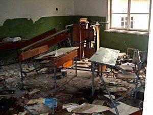 abandoned school desks in ruin