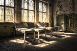 abandoned hospital beds in overgrown room