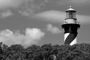 black and white image of St. Augustine Lighthouse behind trees